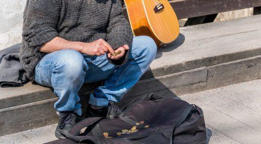 Straßenmusiker zaehlt Geld
