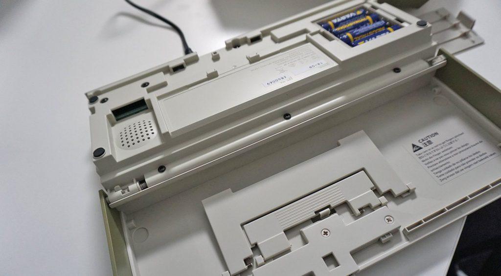 Auf der Unterseite finden sich Batteriefach, Lautsprecher und Aufstellbügel.